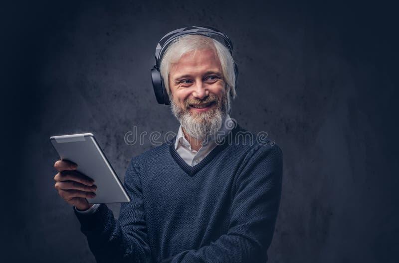 使用有耳机的一名英俊的老人的演播室画象一种片剂在黑暗的背景 库存图片