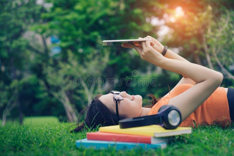 使用有耳机的女孩亚洲人片剂 免版税库存图片