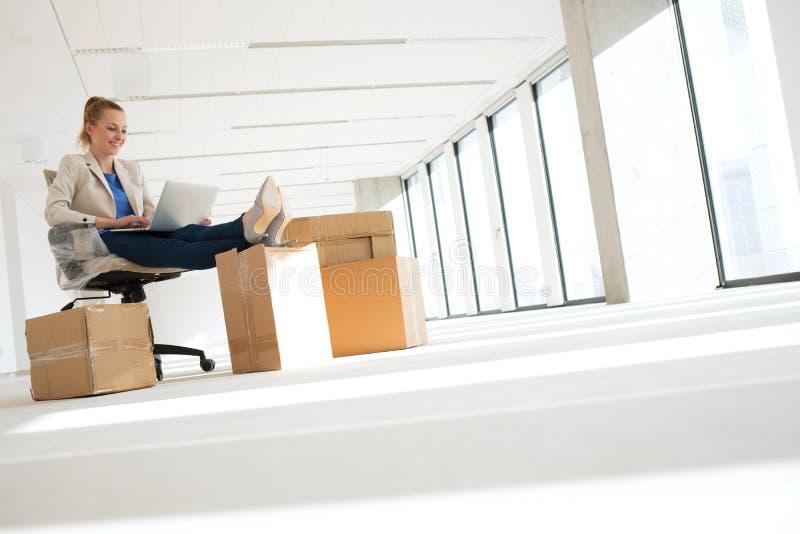 使用有脚的全长年轻女实业家膝上型计算机在移动的箱子在办公室 图库摄影