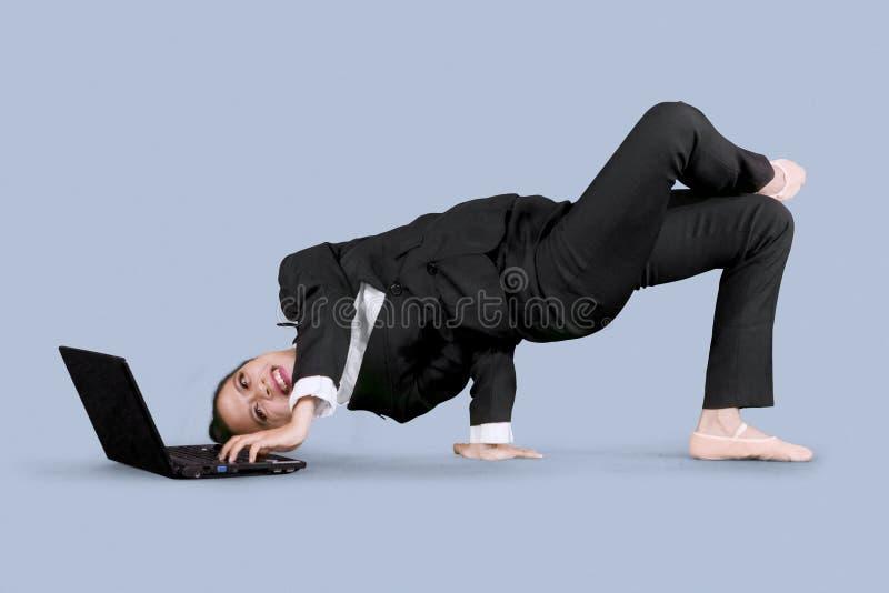 使用有舞蹈姿势的女实业家一台膝上型计算机 库存照片