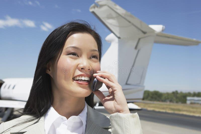 使用有飞机的女实业家手机在背景 免版税库存图片