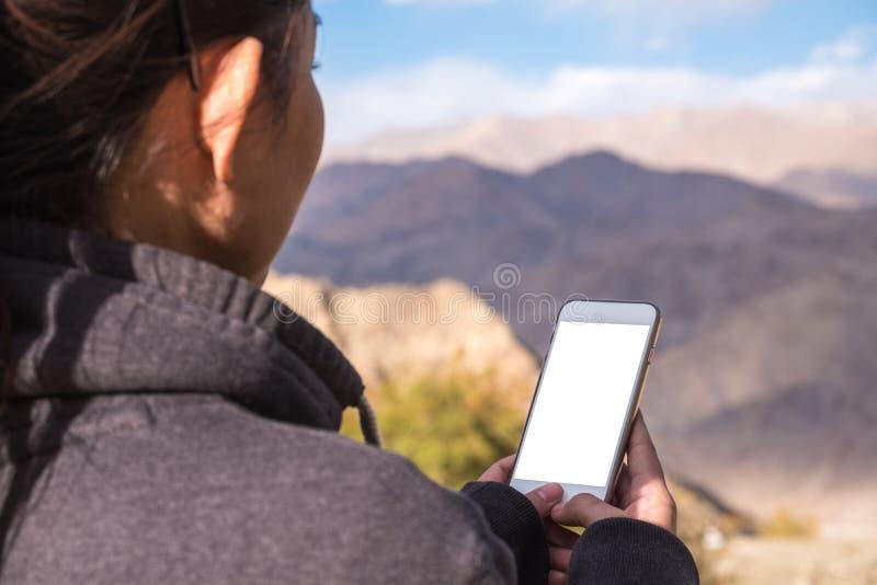 使用有黑屏的妇女白色手机,当站立在山和蓝天前面时 免版税库存图片
