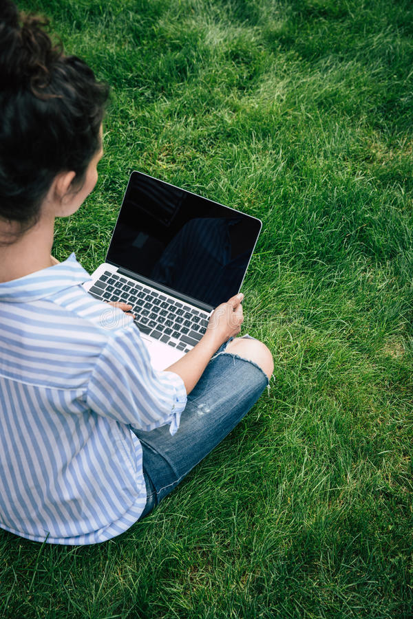 使用有黑屏的深色的女孩膝上型计算机,当坐草时 库存照片