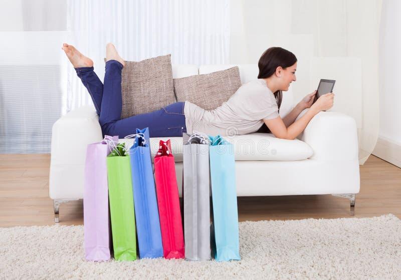 使用有购物袋的妇女数字式片剂在地板上 图库摄影