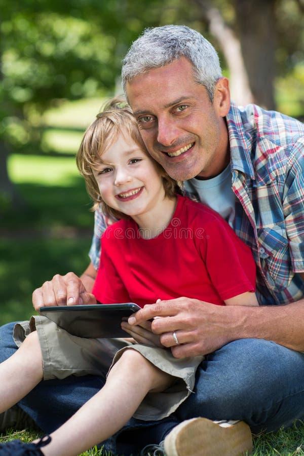 使用有他的儿子的愉快的父亲片剂个人计算机 免版税库存照片