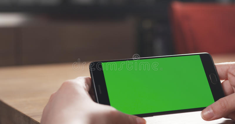 使用有绿色屏幕的女性青少年的女孩智能手机坐在桌 库存照片