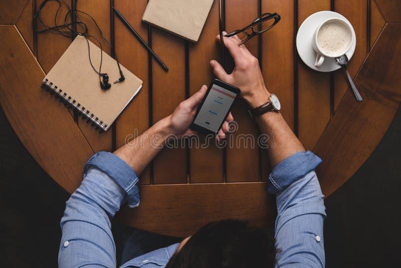 使用有instagram网站的顶上的观点的人智能手机,当坐在桌用咖啡时 免版税库存图片