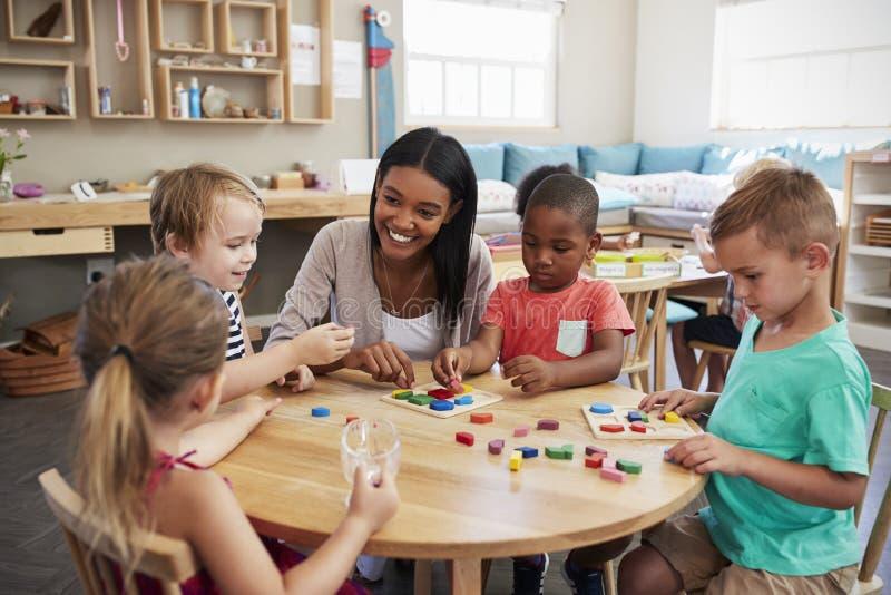 使用木形状的老师和学生在蒙台梭利学校 免版税库存照片
