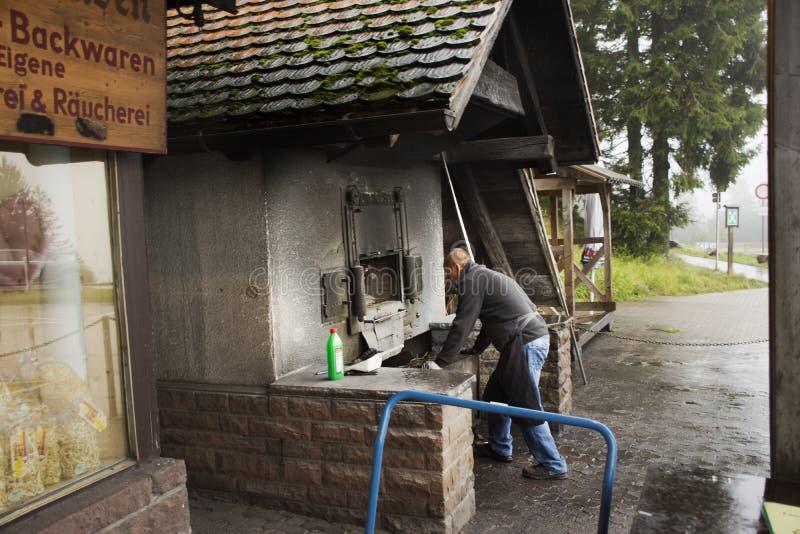 使用木柴火炉老牌烹调面包的德国老人在餐馆 免版税库存照片