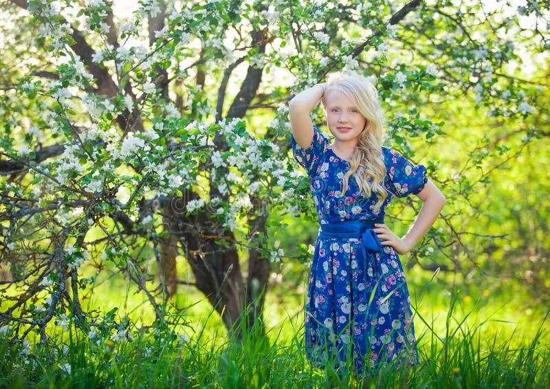 使用本质上的可爱的孩子 逗人喜爱的小孩,使用在美丽的开花的樱桃庭院里的白肤金发的小孩女孩 免版税库存照片