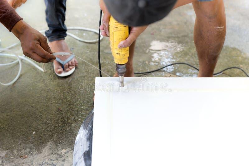 使用机械钻的承包商削减在大理石柜台的一个孔 库存图片