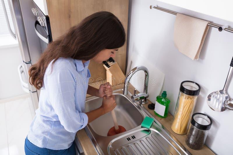 使用柱塞的妇女在封锁的厨房水槽 免版税库存图片