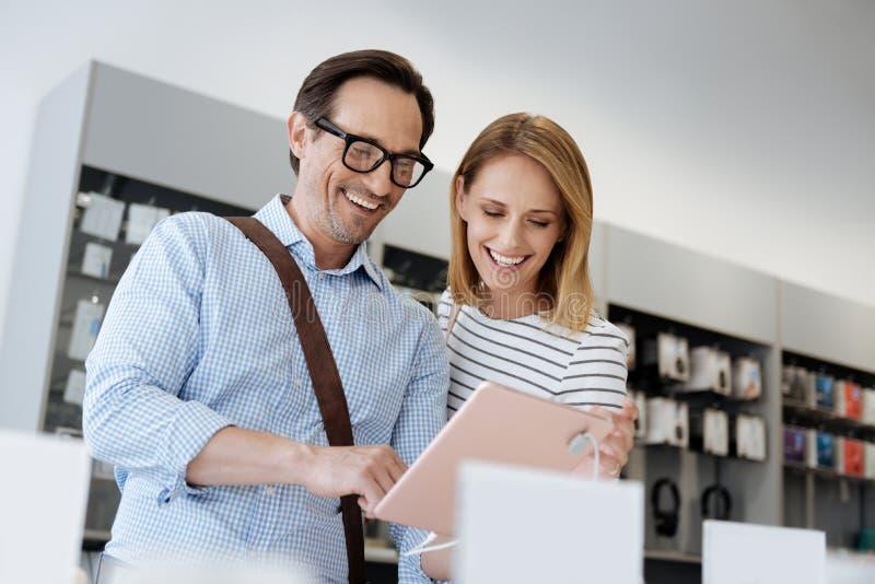 使用模板数字式片剂的激动的已婚夫妇在电子商店 免版税库存照片