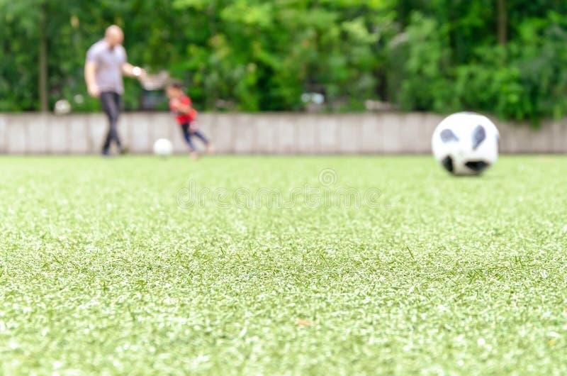 使用橄榄球草坪、的父亲和的孩子  库存图片