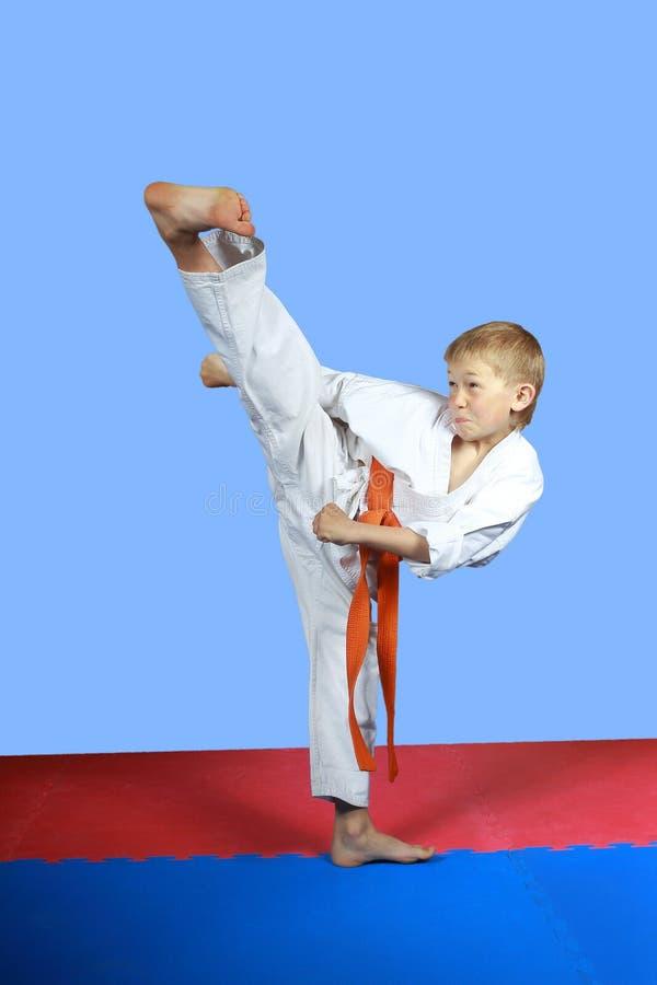 使用橙色传送带男孩训练反撞力yoko-geri 库存照片