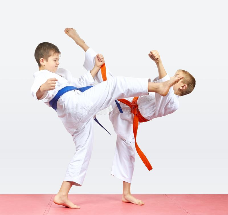 使用橙色和蓝色传送带男孩打解雇腿 免版税库存图片