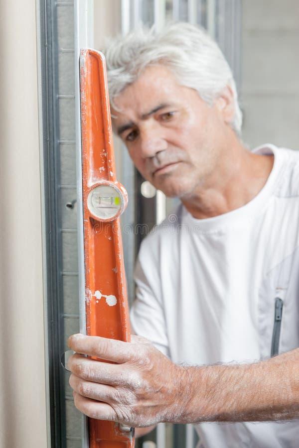 使用橙色水平仪的泥工 库存图片