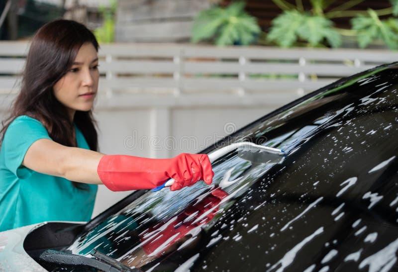 使用橡皮刮板的妇女对汽车洗涤的挡风玻璃  库存照片