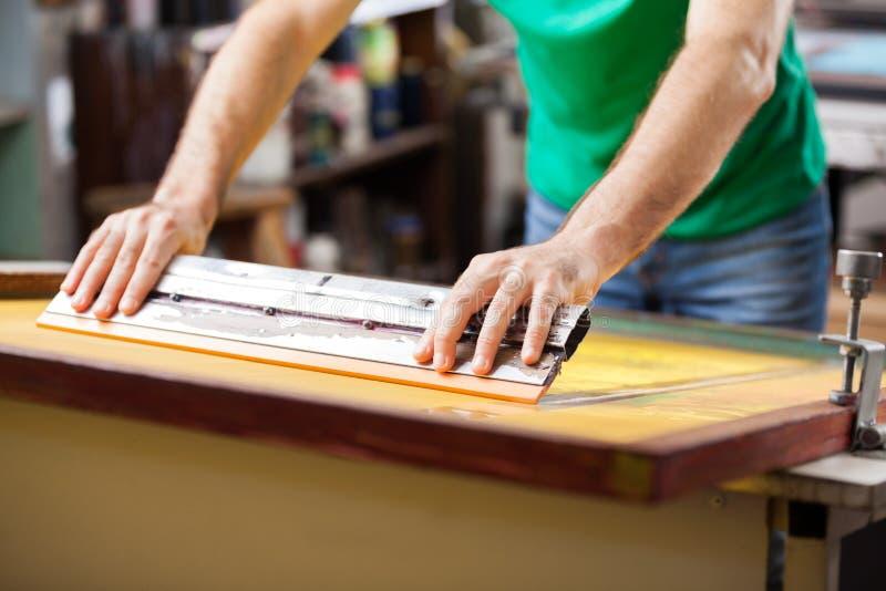使用橡皮刮板的工作者在工厂 库存照片