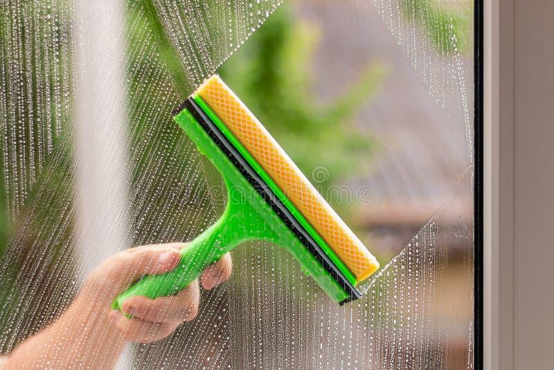 使用橡皮刮板的风窗清洁器洗涤窗口 免版税库存照片