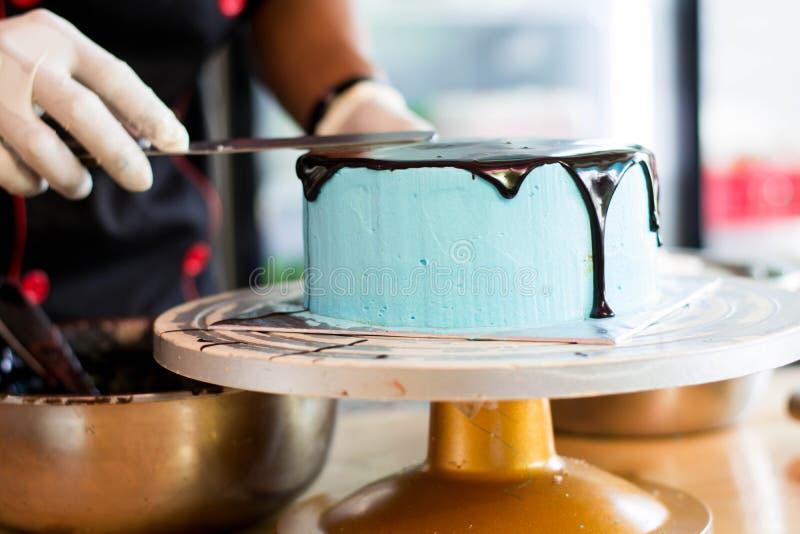 使用橡胶手套的点心师手徒升光滑在圆的蓝色蛋糕的熔化巧克力 库存图片