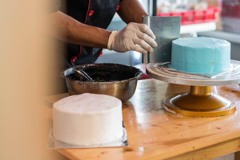使用橡胶手套的点心师手徒升光滑在圆的蓝色蛋糕的熔化巧克力 免版税库存图片