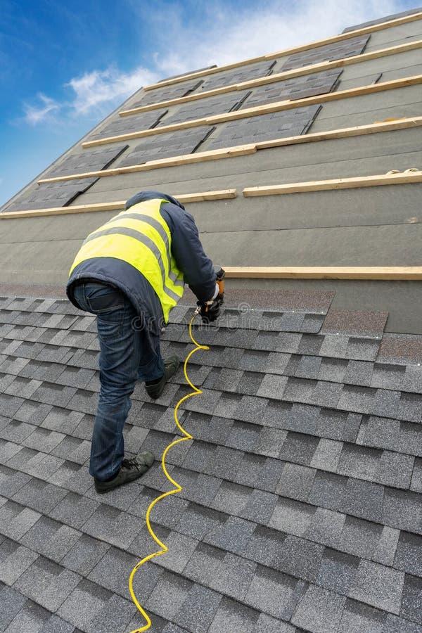 使用气动力学的钉子枪的工作员在新房屋顶安装瓦片建设中 免版税库存图片