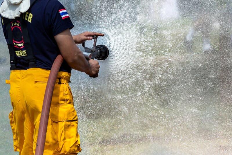 使用水和灭火器,消防员的消防员使用水和灭火器汽车着火, 图库摄影