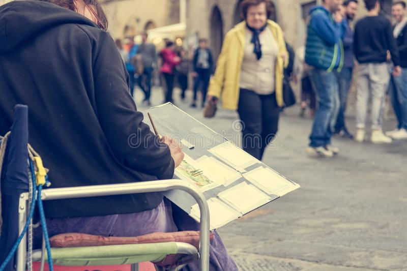使用水性涂料的女性街道艺术家绘纪念品painitng 免版税库存照片
