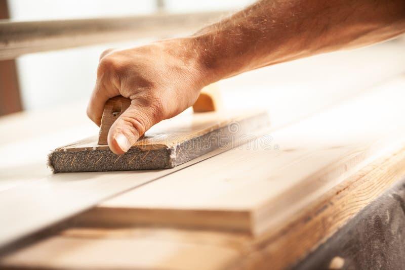 使用沙磨机的木匠在车间使木头光滑 免版税库存图片