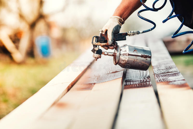 使用油漆枪或喷枪的产业工人为应用油漆 库存图片
