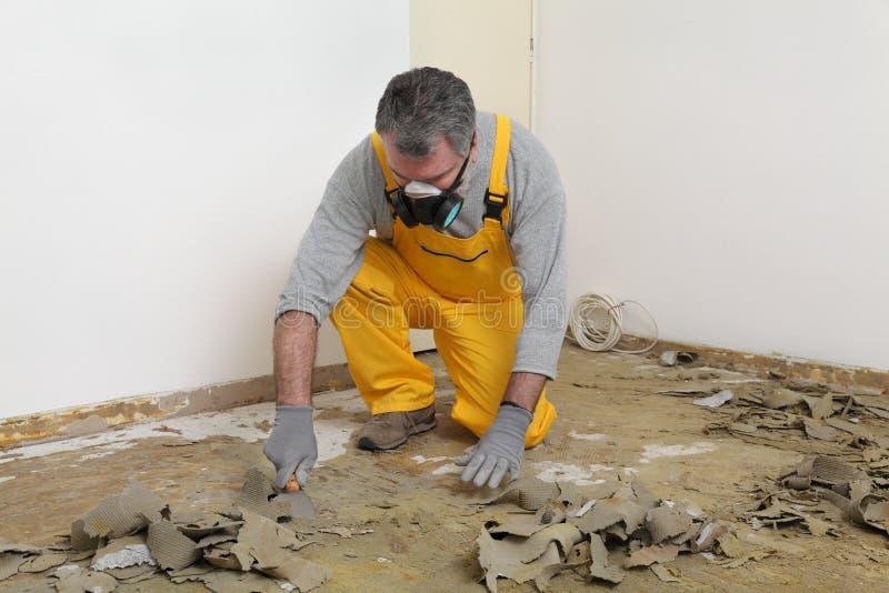 使用油灰刀的工作者为清洗的地板 库存照片
