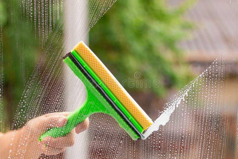 使用洗涤的橡皮刮板的风窗清洁器窗口 免版税库存图片