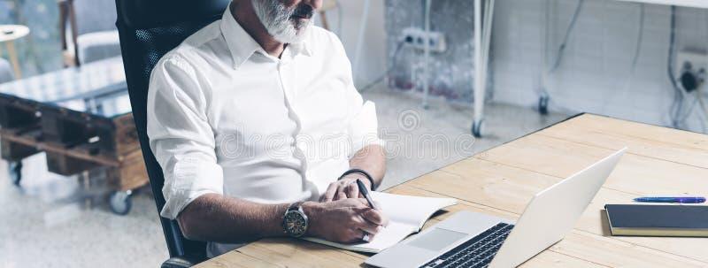 使用流动便携式计算机的可爱和机要成人商人,当工作在木桌上在现代时 库存照片