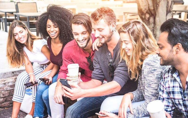 使用流动巧妙的电话的多种族朋友小组在大学学院 免版税库存照片