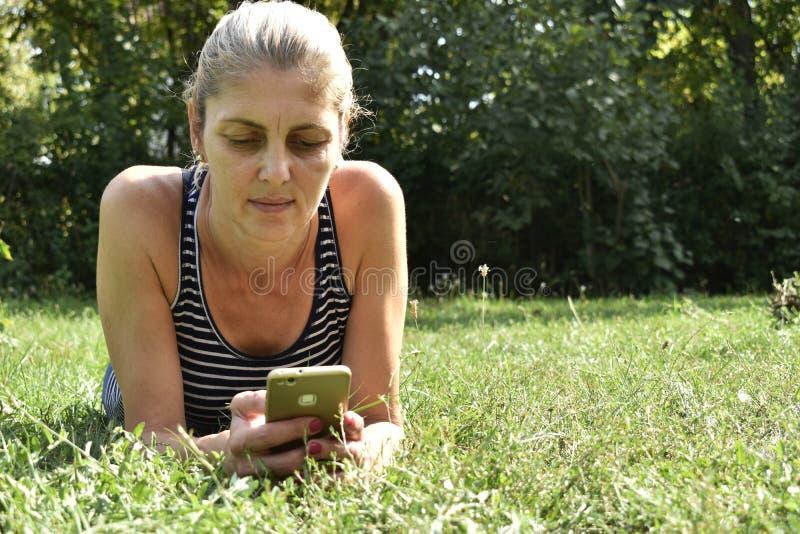 使用流动巧妙的电话的妇女在公园 库存图片