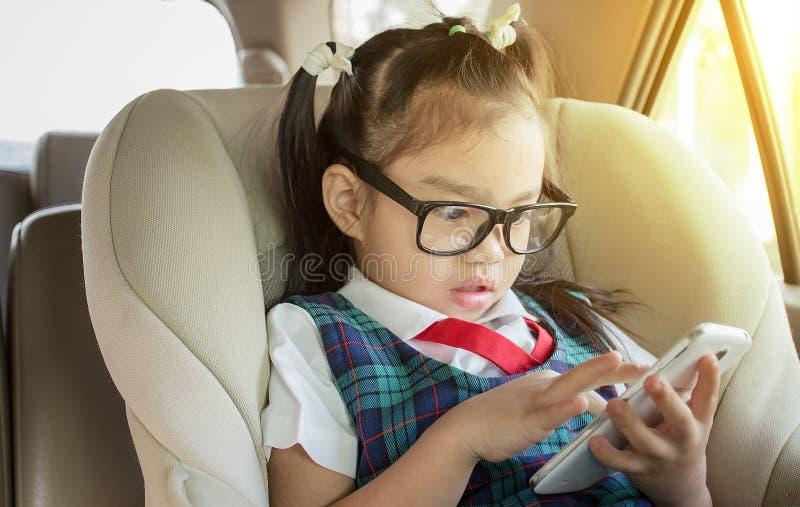 使用流动巧妙的电话的孩子在汽车 免版税库存图片