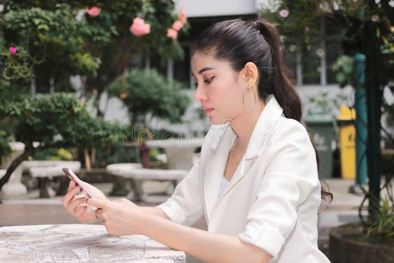 使用流动智能手机的可爱的年轻亚裔妇女 事概念互联网 库存照片
