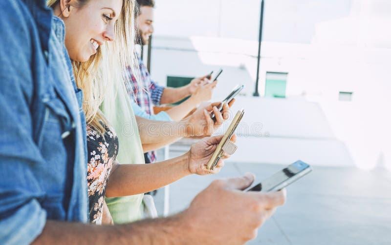 使用流动智能手机的小组朋友室外-获得年轻的学生冲浪在社会媒介网络趋向的乐趣 免版税图库摄影