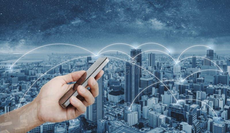 使用流动智能手机的手和网络连接技术在城市 企业网络和互联网连接 免版税库存图片
