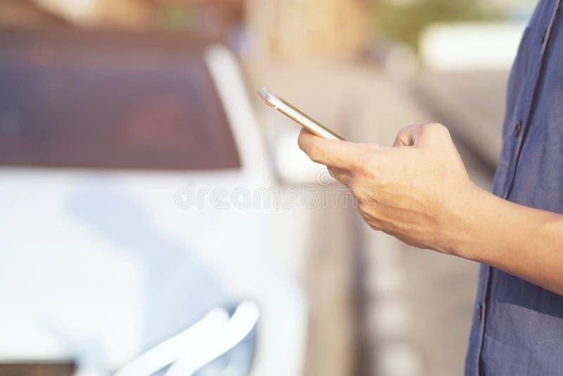 使用流动智能手机的接近的手人人立场在路旁路边 告诉汽车修理师请求帮忙 库存照片