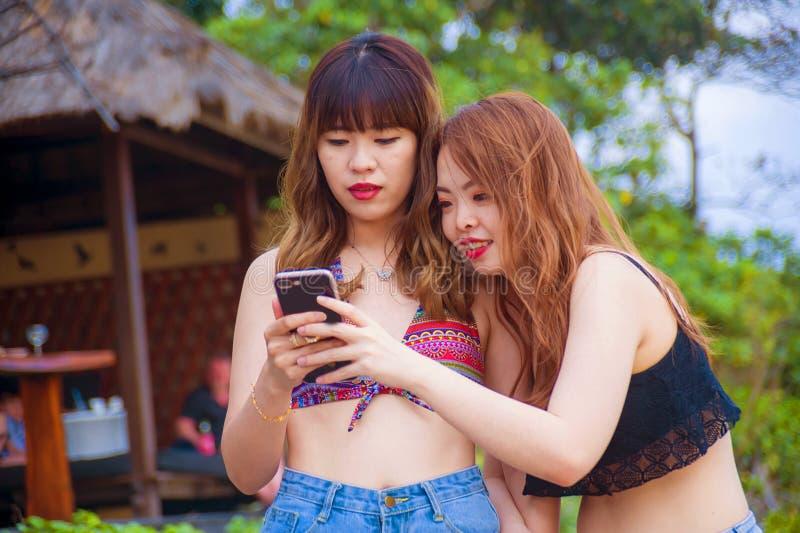 使用流动酸碱度的,互联网两愉快和相当享受暑假的亚裔韩国女朋友一起绊倒在热带海滩 库存图片