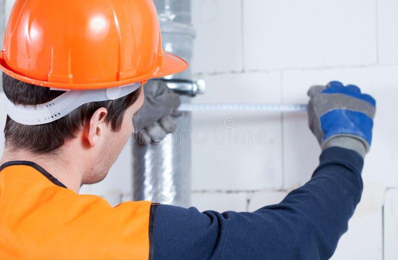 使用测量的磁带的建造者 免版税库存图片