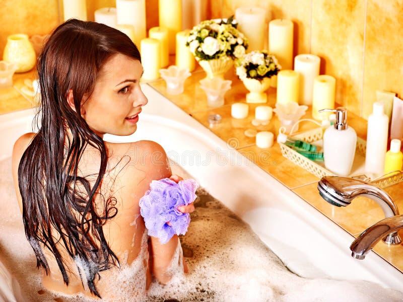 使用浴海绵的妇女在浴缸。 库存图片