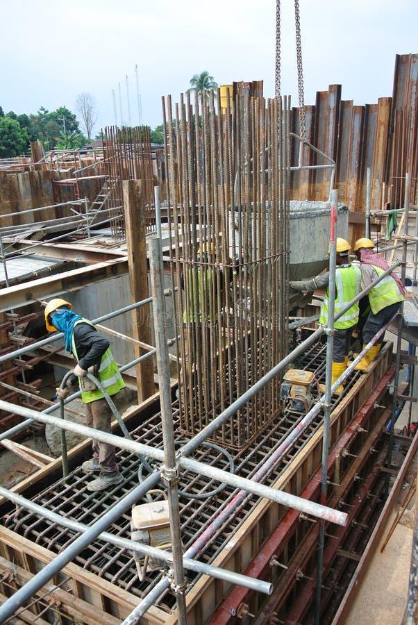 使用混凝土振动器的建筑工人变紧密具体泥浆 库存图片