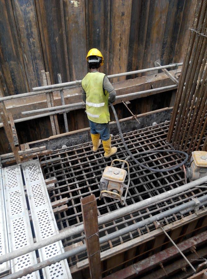 使用混凝土振动器的建筑工人变紧密具体泥浆 免版税库存照片