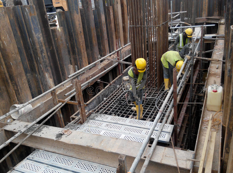 使用混凝土振动器的建筑工人变紧密具体泥浆 免版税库存图片