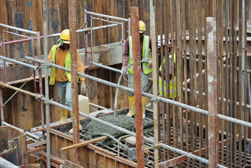 使用混凝土振动器的建筑工人变紧密混凝土 免版税库存图片