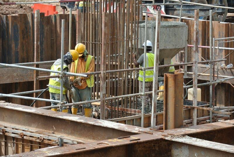 使用混凝土振动器的建筑工人变紧密混凝土 库存照片