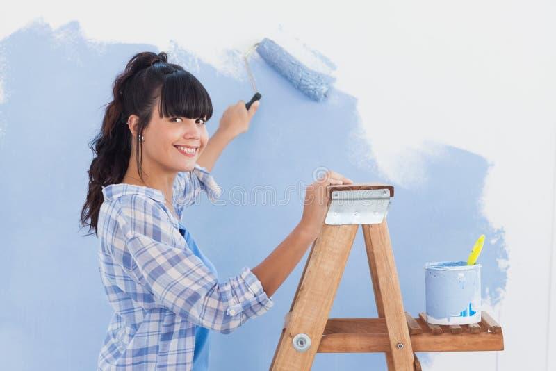 使用漆滚筒的妇女绘墙壁和微笑对照相机 免版税库存图片